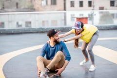 Amis ayant l'amusement avec la planche à roulettes dehors Photo libre de droits