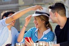 Amis ayant l'amusement avec le chapeau blanc dans la rue Photographie stock libre de droits