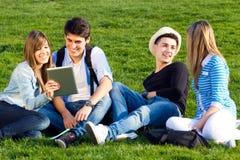 Amis ayant l'amusement avec les comprimés numériques Images libres de droits