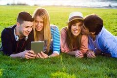 Amis ayant l'amusement avec les comprimés numériques Photos stock