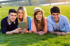 Amis ayant l'amusement avec les comprimés numériques Photo stock