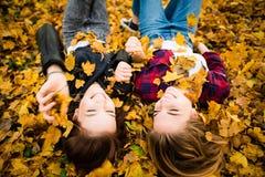 Amis ayant l'amusement dans des feuilles Photo libre de droits