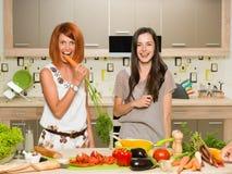Amis ayant l'amusement dans la cuisine Images libres de droits