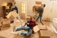 Amis ayant l'amusement dans la nouvelle maison tout en déballant des choses Photo libre de droits