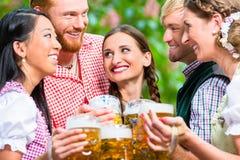 Amis ayant l'amusement dans le jardin de bière tout en faisant tinter des verres Image libre de droits