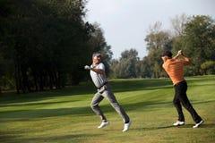 Amis ayant l'amusement dans le terrain de golf Image stock