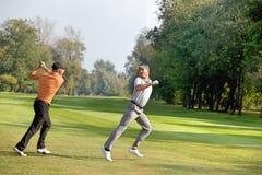 Amis ayant l'amusement dans le terrain de golf Photo libre de droits