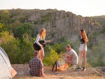 Amis ayant l'amusement dans un parc Randonneurs détendant sur un coucher du soleil sur un fond naturel Copiez l'espace Image libre de droits