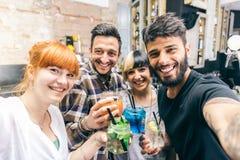 Amis ayant l'amusement dans une barre avec des cocktails Image stock