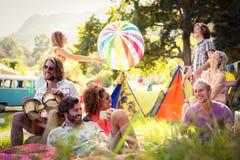 Amis ayant l'amusement ensemble au terrain de camping Image libre de droits