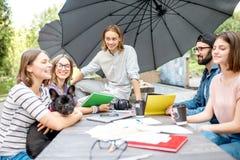 Amis ayant l'amusement ensemble pendant une étude dehors Photo stock