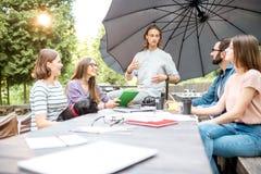 Amis ayant l'amusement ensemble pendant une étude dehors Photo libre de droits