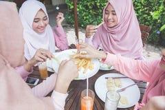 Amis ayant l'amusement ensemble tout en prenant le déjeuner Images libres de droits