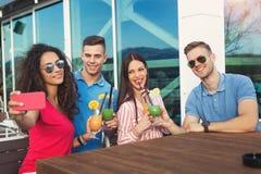 Amis ayant l'amusement et buvant des cocktails extérieurs Images libres de droits
