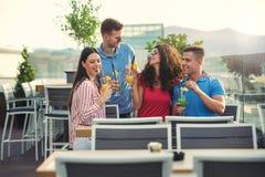 Amis ayant l'amusement et buvant des cocktails extérieurs Image libre de droits