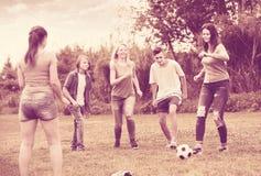 Amis ayant l'amusement et donnant un coup de pied le football Photographie stock