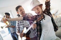 Amis ayant l'amusement et faisant la fête dans la maison et jouant la musique Photographie stock libre de droits