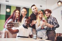 Amis ayant l'amusement et faisant le selfie au restaurant Deux garçons et quatre filles buvant de la bière et mangeant de la pizz Image stock