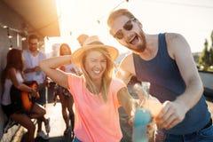 Amis ayant l'amusement et le boire extérieurs sur une réunion de dessus de toit Photos stock
