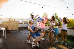 Amis ayant l'amusement et le boire extérieurs sur une réunion de dessus de toit Photo stock