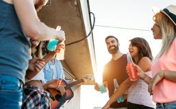 Amis ayant l'amusement et le boire extérieurs sur une réunion de dessus de toit Image stock