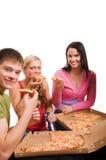 Amis ayant l'amusement et mangeant de la pizza Photo libre de droits