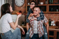 Amis ayant l'amusement et mangeant la partie de pizza à la maison Photos stock
