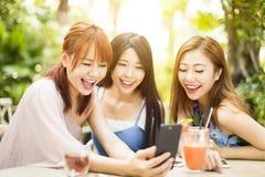 Amis ayant l'amusement et regardant le téléphone intelligent Image stock