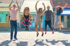 Amis ayant l'amusement et sautant au beau jour ensoleillé Photos stock