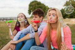 Amis ayant l'amusement et soufflant des bulles de savon dans le parc Photo libre de droits
