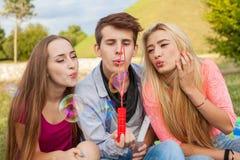 Amis ayant l'amusement et soufflant des bulles de savon dans le parc Photo stock