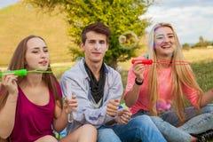 Amis ayant l'amusement et soufflant des bulles de savon dans le parc Photos stock