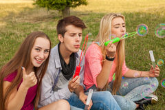Amis ayant l'amusement et soufflant des bulles de savon dans le parc Photographie stock libre de droits