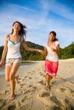 Amis ayant l'amusement exécuter le long de la plage Photos libres de droits