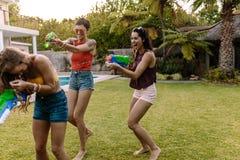 Amis ayant l'amusement jouant avec des armes à feu d'eau Image stock