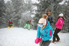Amis ayant l'amusement jouant avec la boule de neige dans la neige sur W froid Photos stock