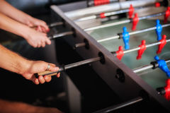 Amis ayant l'amusement jouant le foosball de table Photo stock