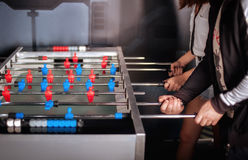 Amis ayant l'amusement jouant le foosball de table Images stock
