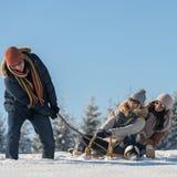 Amis ayant l'amusement l'hiver ensoleillé de traîneau Image stock