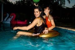 Amis ayant l'amusement pendant la réception au bord de la piscine de soirée Images stock