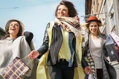 Amis ayant l'amusement pendant les achats dans la ville Photo stock