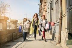 Amis ayant l'amusement pendant les achats dans la ville Image stock