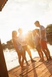 Amis ayant l'amusement près du lac Photos libres de droits