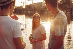 Amis ayant l'amusement près du lac Photo stock