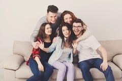 Amis ayant l'amusement, prenant la partie de selfie à la maison Photos stock