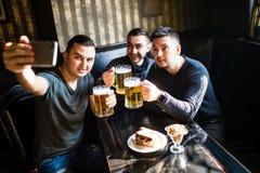 Amis ayant l'amusement prenant le selfie et buvant de la bière pression dans le bar Photo stock