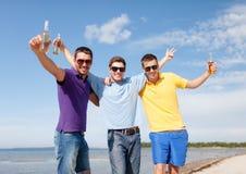 Amis ayant l'amusement sur la plage avec des bouteilles de bière Image libre de droits