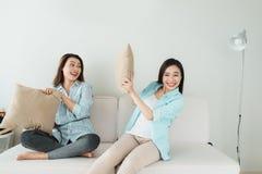 Amis ayant l'amusement sur le divan et faisant le combat d'oreiller Photos stock