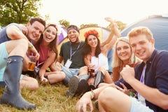 Amis ayant l'amusement sur le terrain de camping à un festival de musique Image stock