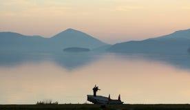 Amis ayant l'amusement sur un pilier prespa de lac, Macédoine, coucher du soleil sur un lac, Photos libres de droits